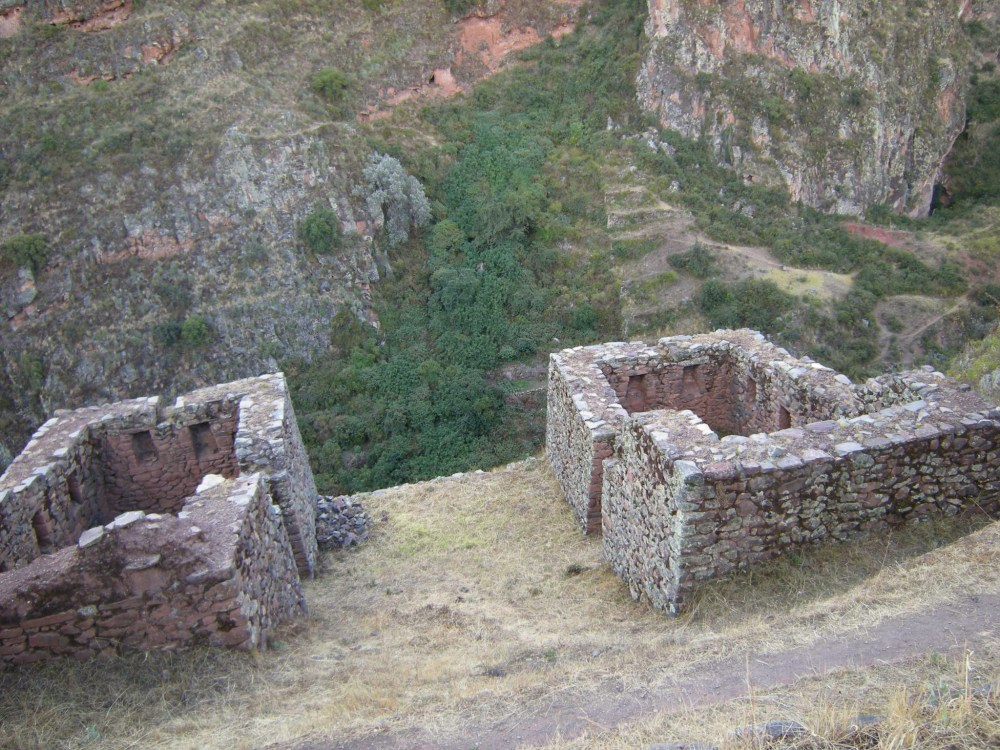Ruins of homes perched on the edge of the mountainside.