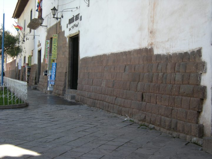 Cusco street with partially exposed Inca wall.