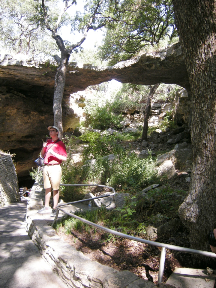 A tour guide gives instructions. Behind her is the natural bridge for which the caverns are named.