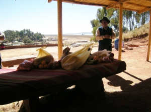 The mayor of the village stands near the table of food that we bought in Puno.