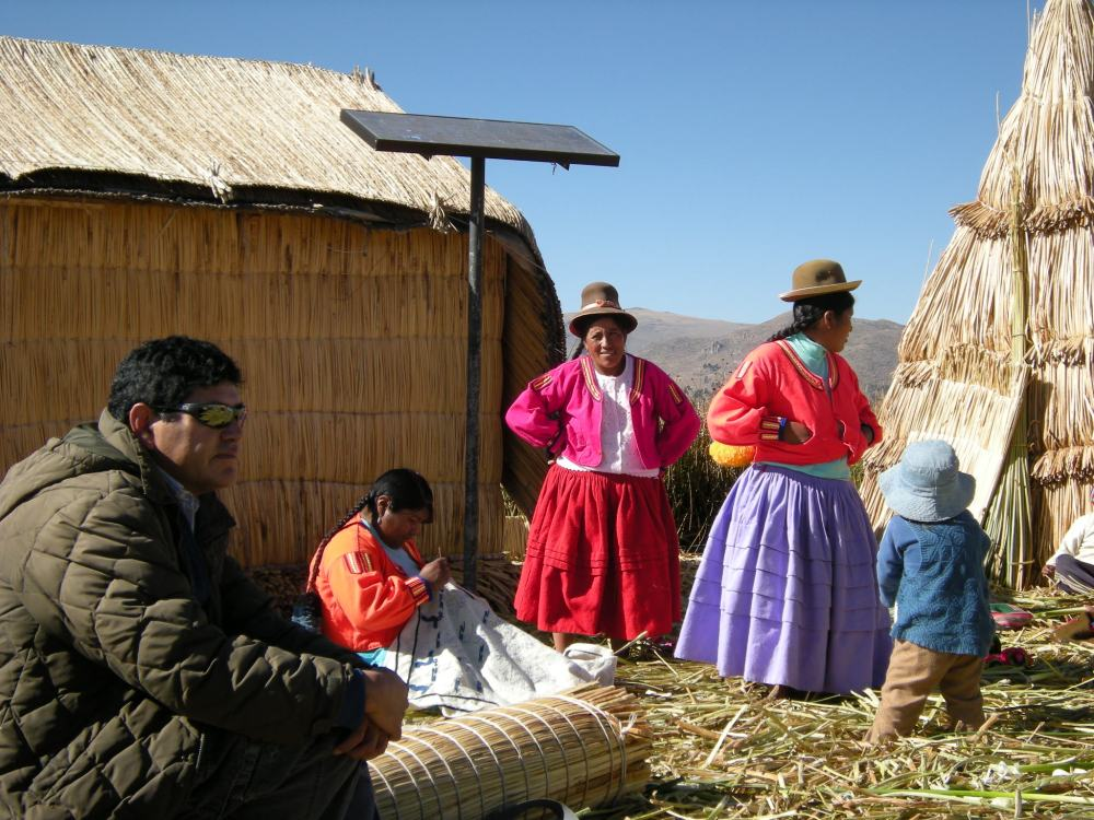 Traditionally clothed women invite us to come into their homes. Note the black pole with a panel on top - it is a solar panel! The Uros use solar power for small appliances such as radios or TVs.