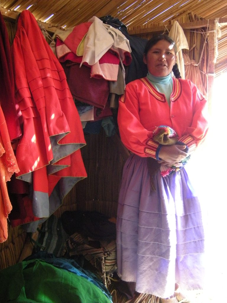 Inside one of the houses. I am invited to try on the woman's traditional clothing. I decline but others give it a try.