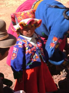 This little girl wears a colorful jacket and the cap worn by single girls, meant to resemble the kantu flower.