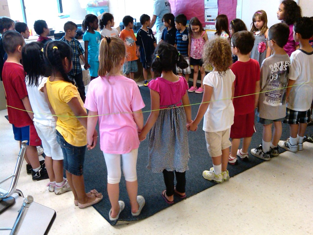 Last day of kindergarten - the children stood in a circle holding hands. The teacher surrounded them with a string - when she cut it, they'd no longer be kindergartners!