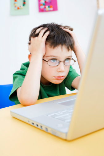 Frustrated boy using laptop computer