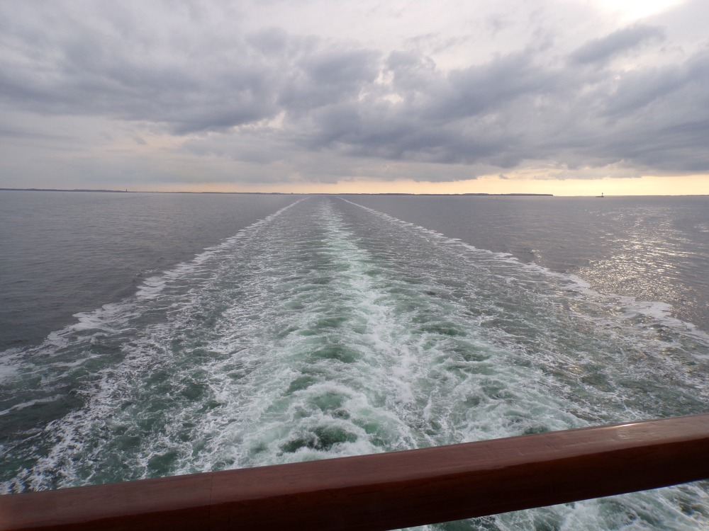 The ship's wake, leading out to the horizon in the sunset.