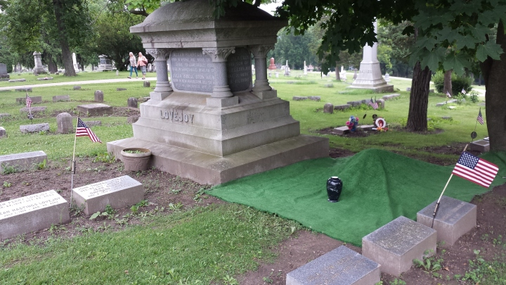 The urn with Mother's ashes sits next to her covered grave.