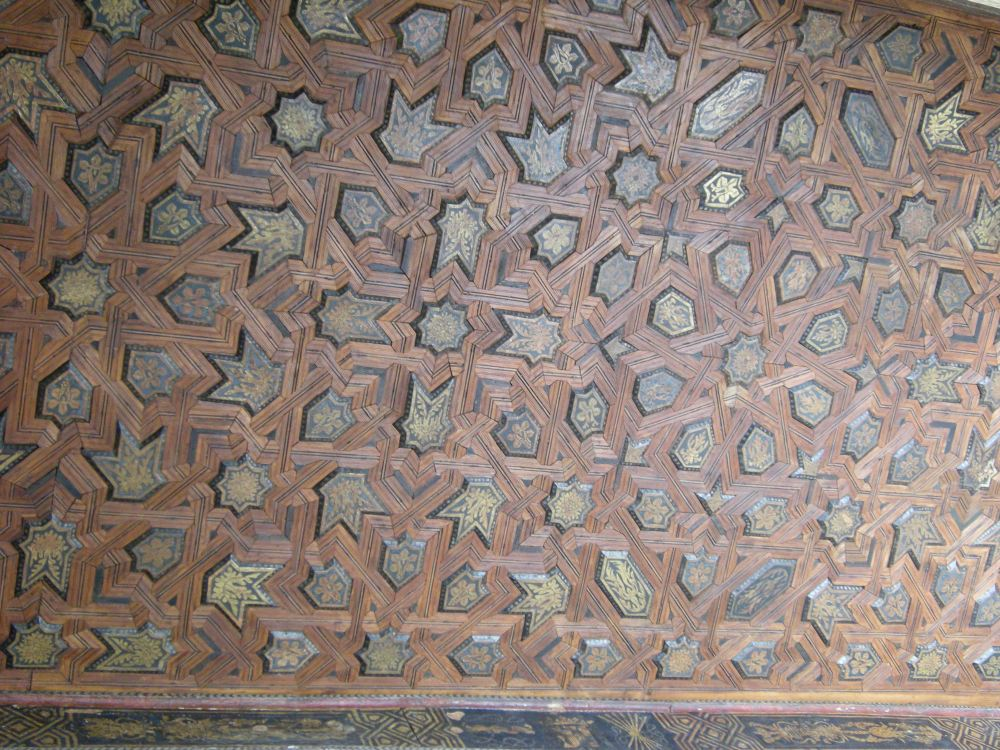 "Detail of ceiling. The ceiling of the Throne Hall is totally original, and it dates from the latter part of the 14th century. It is all made of wood, with cut pieces in mosaics to resemble a heaven full of stars. This represents the Islamic concept of ""seventh heaven"" (from which the saying is derived). In Islam, when you die you go to first heaven, then to 2nd, then to 3rd, etc., until you get to 6th heaven. To get to seventh heaven, which is Paradise, you must break through the stars and enter Paradise."