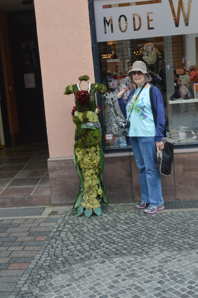 I'm posing next to an unusual sculpture made of plants, outside a shop.
