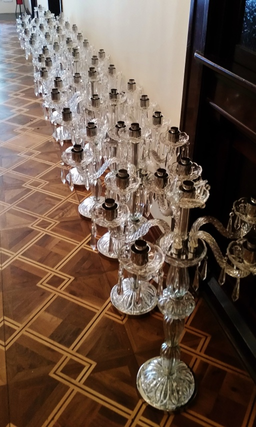 candelabras lined up in the hallway presumably for the wedding