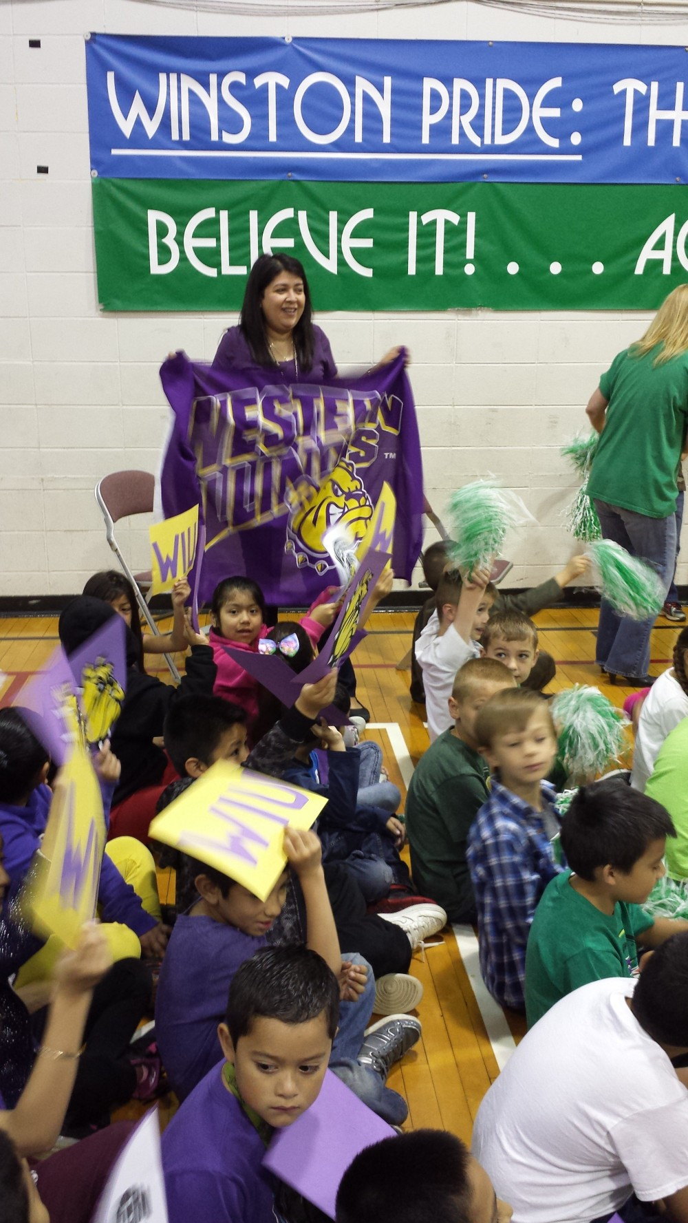 Sandy Rywelski holds up WIU flag next to her class.