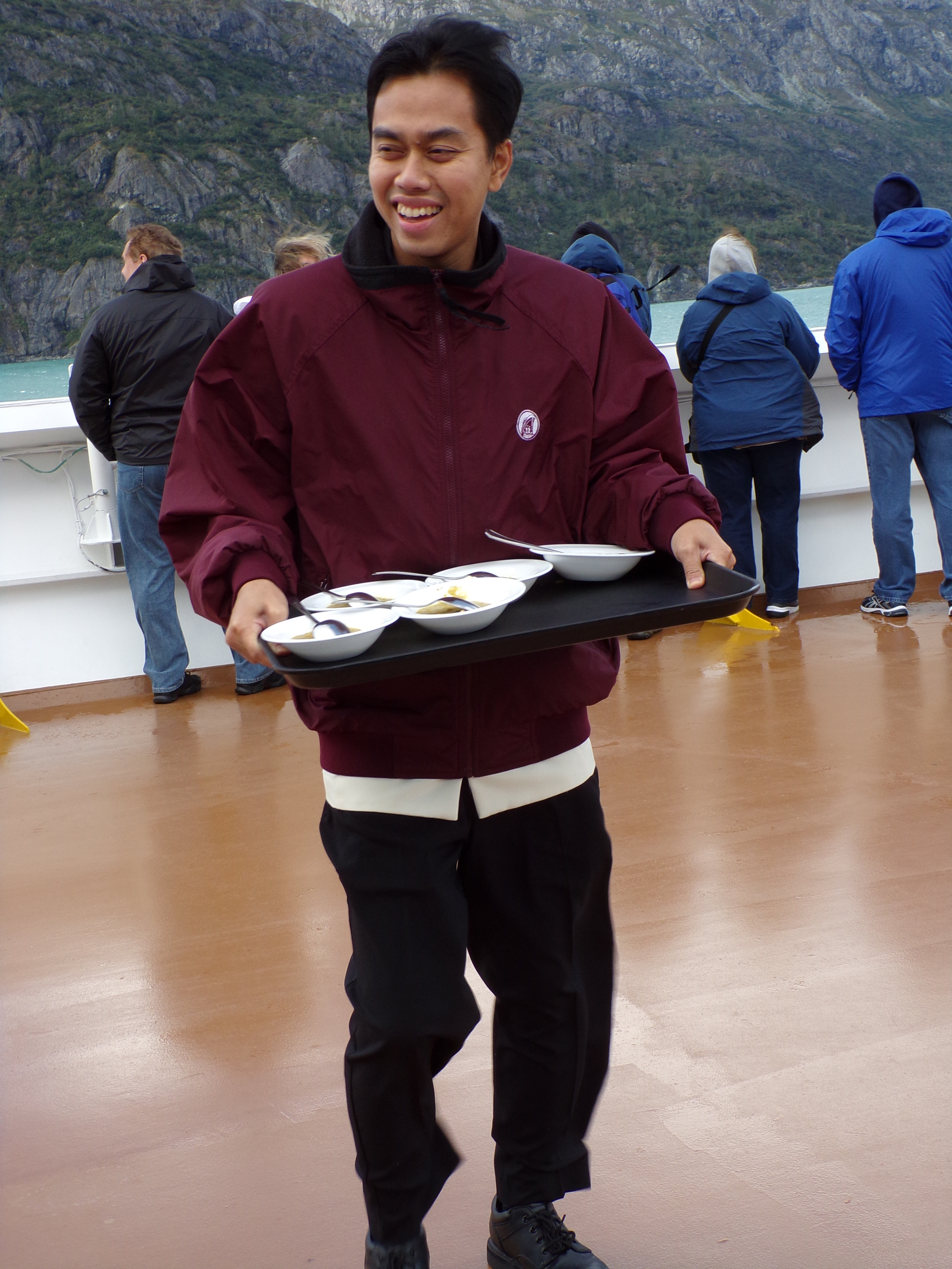 The steward holds on tight to the tray of soup.